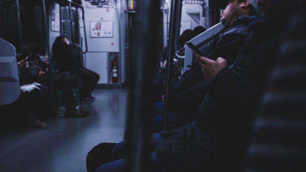 疲れ果てて電車で眠るサラリーマン